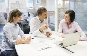 stock-photo-33531374-work-team-in-meeting-room-working-on-laptop
